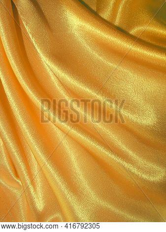 Beautiful Draped Golden Silk Fabric Background. Fabric Texture