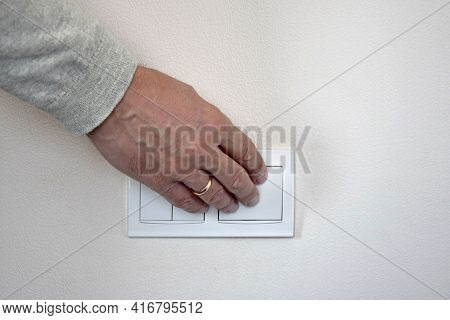 Male Hand Presses Button Of White Switch Mounted On Light Wall. Close-up. Selective Focus. Copy Spac