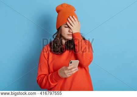 Frustrated Female Wearing Casual Clothing, Covering Face With Palm, Holding Phone In Hands, Forget S