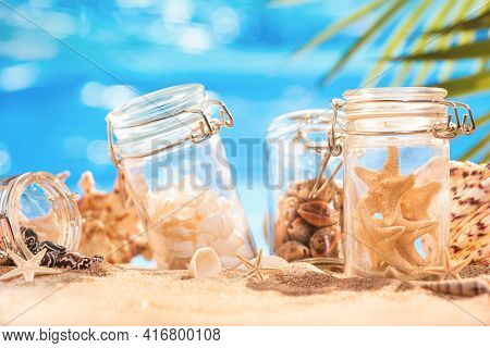 Various Shells And Starfish In Jars On The Azure Seashore. Vacation Shells. Nostalgia For A Tropical