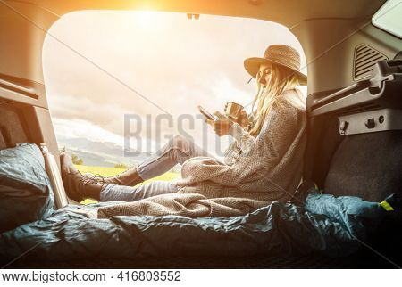 Girl resting in her car with her phone. Woman hiker, hiking backpacker traveler camper in sleeping bag relaxing on top of mountain. Road trip, Health care, authenticity, sense of balance and calmness.