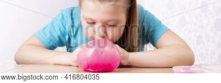 A Blonde Child Blows A Slime Bubble. Play A Slime Toy. Making Slime At Home
