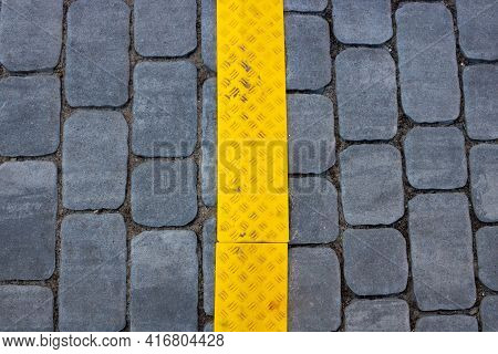 The Texture Of Gray Paving Slabs With A Yellow Stripe On The Street, A Promising View. Cement Brick
