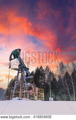 Oil Pumpjack Winter Working. At The Orange Sunset Dawn Of The Sky With Clouds. Oil Rig Energy Indust