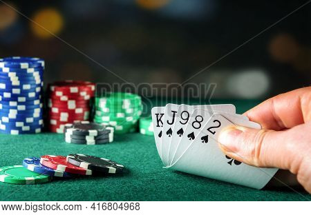 Poker Cards With Flush Combination. Close Up Of Gambler Hand Takes Playing Cards In Poker Club
