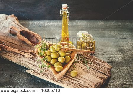 Green Olives In A Heart-shaped Wooden Bowl On A Wooden Background, A Bottle Of Olive Oil With Olives