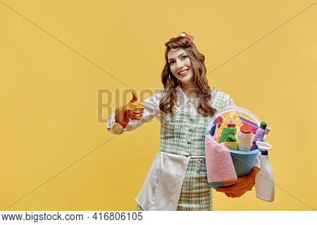 Happy Cleaning Woman With Cleaning Tools In The House Shows A Super Gesture.