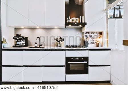 Assorted Cookware And Appliances Placed On Counters With White Cabinets Above In Contemporary Kitche