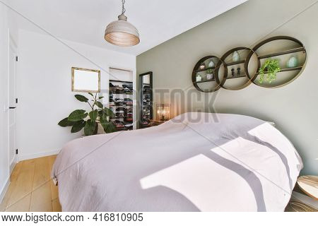 Sunlit Bed Covered With Blanket In Light Contemporary Bedroom With Shelves And Decorations