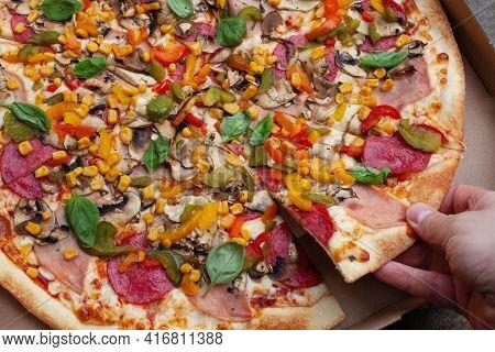 Hand Grabbing A Slice Of Pizza Dough