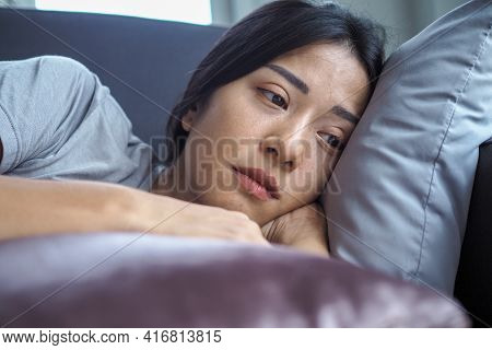 Asian Woman Sitting Inside The House Looking Out At The Window. Woman Confused, Disappointed, Sad An