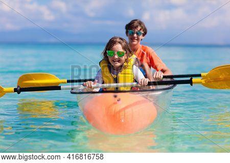 Kids Kayaking In Ocean. Children In Kayak In Tropical Sea. Active Vacation With Young Kid. Parents,
