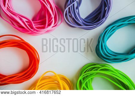 Top View Of Colorful Rubber Bands Isolated On White. Rainbow Elastic Rubber Bands On White. Close Vi