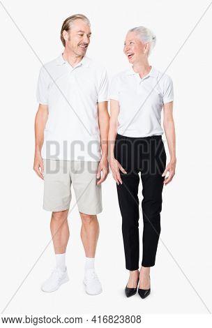 Happy senior couple in white polo shirts with design space studio portrait full body