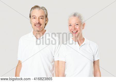 Happy senior couple in white polo shirts with design space studio portrait