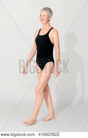 Mature woman in black design one-piece swimsuit summer apparel full body