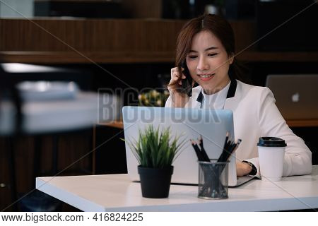 Portrait Of Young Woman Smiling Cheerful Entrepreneur In Office Making Phone Call While Working With
