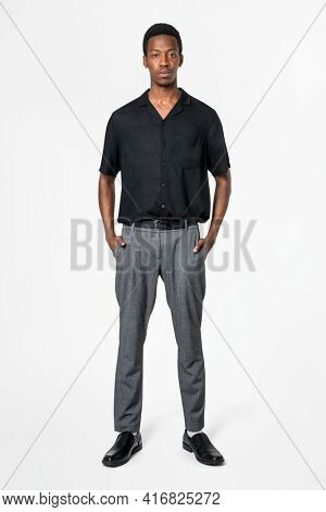 African American man in black shirt and gray slacks business wear full body