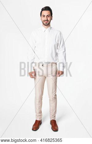 Man in white shirt and beige slacks full body