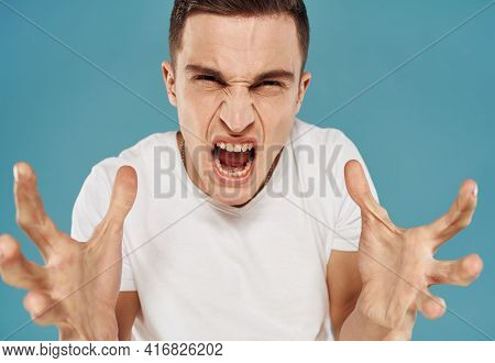 Man In T-shirt Emotions Gestures With Hands Displeasure Blue Background