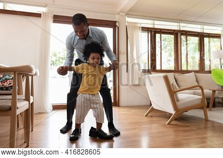 Smiling African Little Child Having Fun Stepping With His Dad Shoe In Living Room At Home. Happy Sma