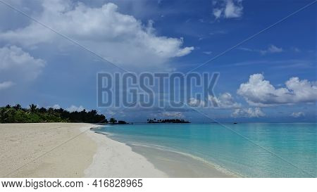 Calm Aquamarine Ocean And Clean Sandy Beach. There Are No People. In The Distance, Tropical Vegetati