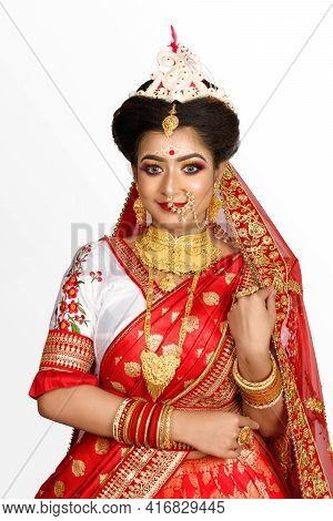 Stunning Indian Bride Dressed In Red Traditional Banarasi Sari Embroidered With Gold Jewellery And A