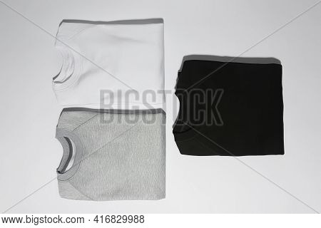 Flat Lay Of Three Perfectly Folded Monochrome Sweatshirts Gray, Black And White Isolated Over White