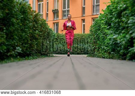 Cant Live Without Sport. Young Disabled Woman In Sportswear Smiling While Running Outdoors. Disabled