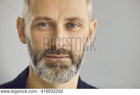 Close Up Portrait Of Happy Bearded Mature Business Man On Grey Studio Background