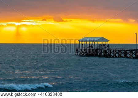 Adelaide, Australia - April 11, 2021: People Walking Along The Henley Beach Jetty While Watching Sto