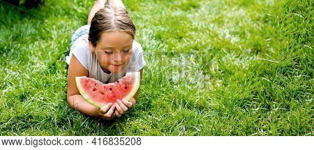 Portrait Of A Pretty Girl 7-8 Years Old Eating A Piece Of Watermelon On The Grass In The Garden. Sum