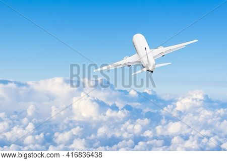 The Plane Flies High In The Sky Among The Clouds