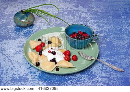 Sweet dumplings stuffed with curd served with sour cream, strawberries, black and red currants.