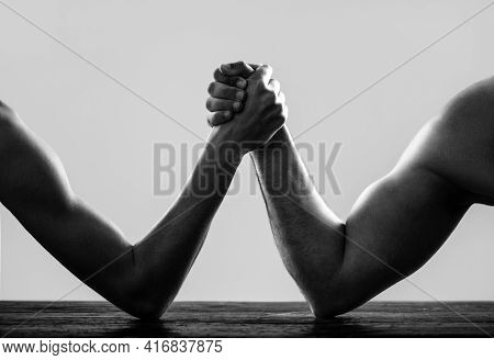 Arms Wrestling Thin Hand And A Big Strong Arm In Studio. Arm Wrestling. Heavily Muscled Man Arm Wres