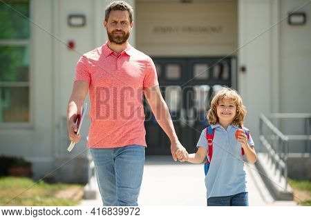 Father Walking To School With Child. Parent And Pupil Of Primary School Go Hand In Hand. First Day A