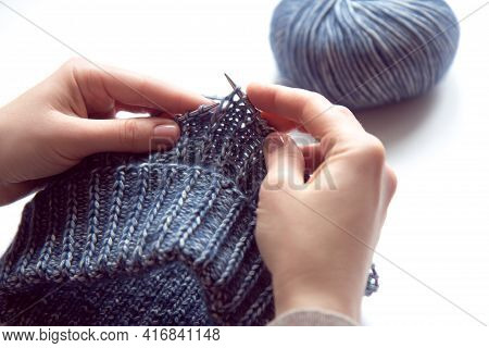 Female Hands With Knitting Needles To Knit Wool Violet Sweater And Tangle Of Woolen Thread On White