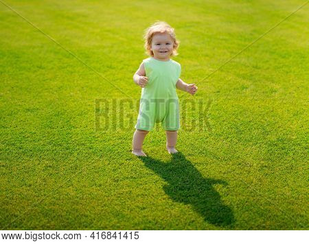 Little Baby Learning To Crawl Steps On The Grass. Concept Childrens Months. Happy Child Playing On G