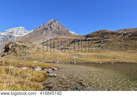 View On Lake In Vanoise National Park In France With Snowy Mountain Background Under Blue Sky