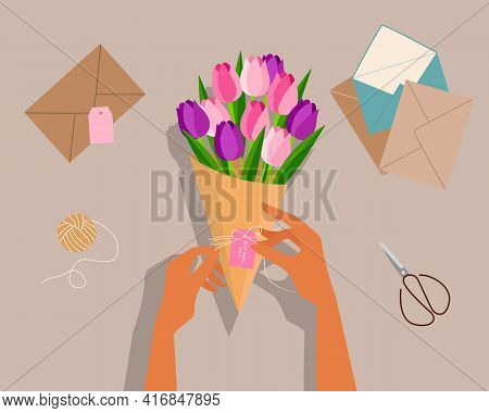 Girl Wrapping Tulip Bouquet To Her Mother, Top View Of Desk, Scissors, Envelope, Flower. Happy Mothe