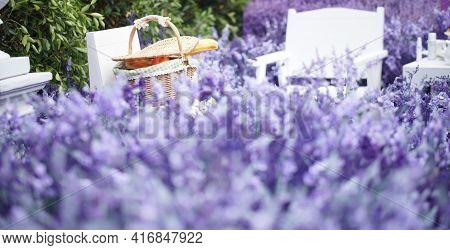 Orange And Bread In Wicker Rattan Basket For Picnic In Lavender Flower Field