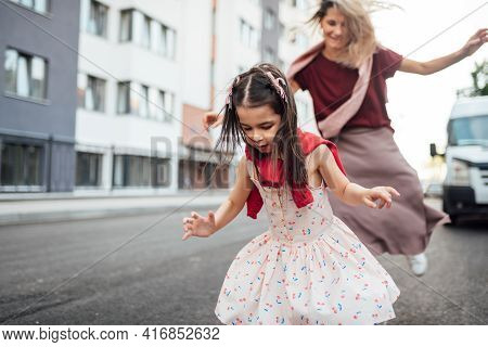 Horizontal Outdoor Image Of A Happy Little Girl Playing Hopscotch With Her Mother On Playground Outd