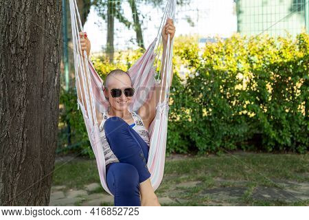 Young Adult Happy Short Haired Shaved Bald Attractive Woman Chilling Enjoy Relaxing Sitting In Fabri