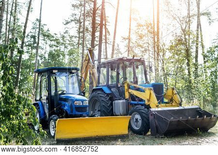 Two Small And Big Modern Tractors Parked At Backyard Near Forest Farm At Countryside. Residential Ho