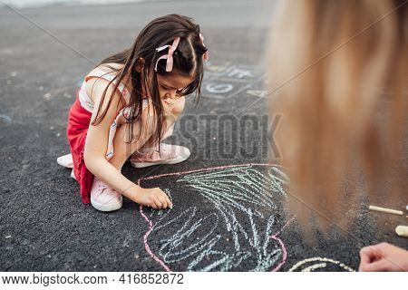 A Cute Little Girl And Mother Drawing With Colorful Chalks On The Playground. Child Playing With Her