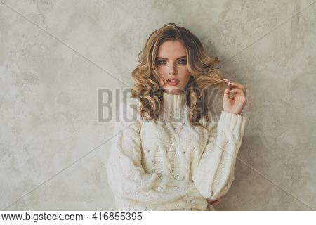 Beautiful Young Blonde Woman With Healthy Curly Hair In White Sweater On Gray Background