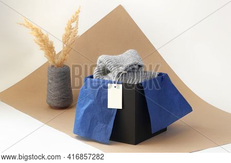 White Blank Paper Logo Tag On A Grey Knitted Scarf In A Black Box And Blue Tissue Paper And Dried Pa