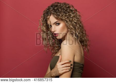 Beautiful Woman Fashion Model With Curly Hairstyle On Red Background