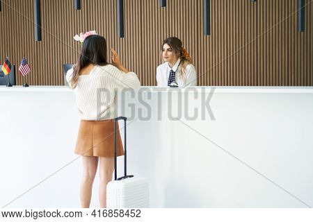 Female tourist waiting at reception desk in hotel