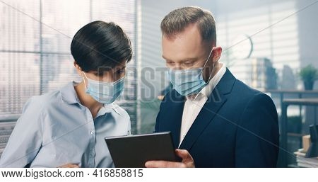 Close Up Portrait Of Caucasian Young Male And Female Co-workers In Medical Masks Standing In Office